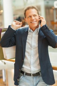 Человек за покупками. веселый зрелый мужчина держит сумки и разговаривает по мобильному телефону, стоя в торговом центре