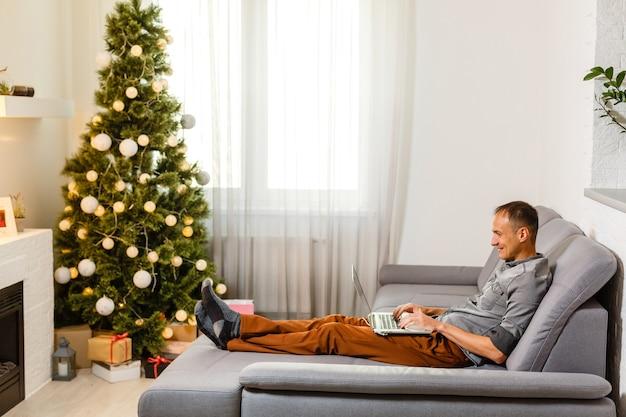 Мужчина покупает рождественские подарки онлайн