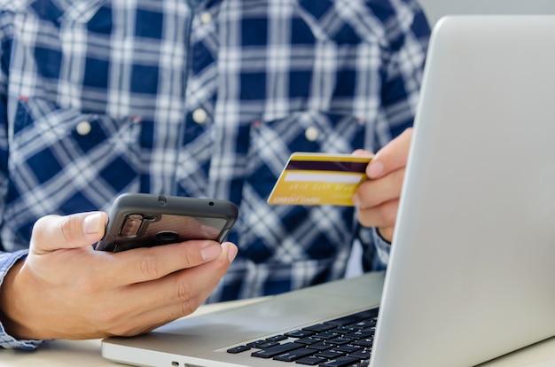 Человек, делающий покупки онлайн, используя ноутбук с кредитной картой. руки, держащей кредитную карту и смартфон.