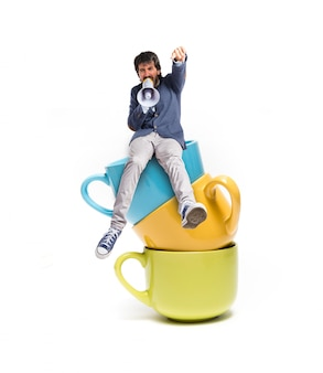 Man shouting and sitting on cups of coffee
