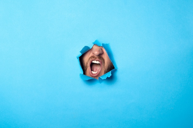 Man shouts from a hole on blue