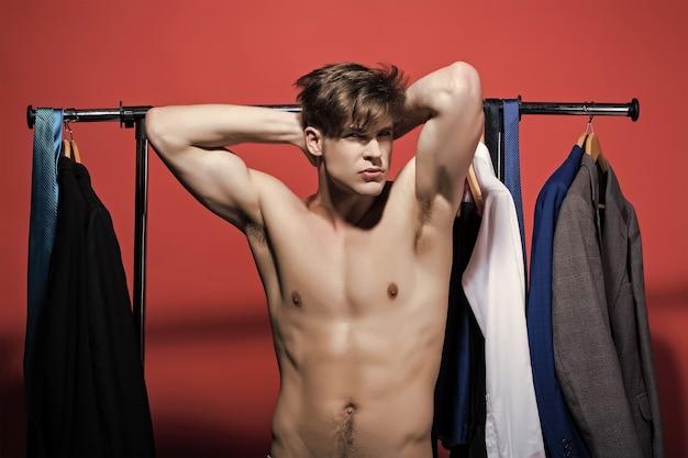 남자 빨간색 표면에 섹시한 몸통 근육 팔을 보여 패션 스타일 개념 잘 생긴 자신감 젊은 남자 섹시한 근육 남성 모델 강한 누드 몸