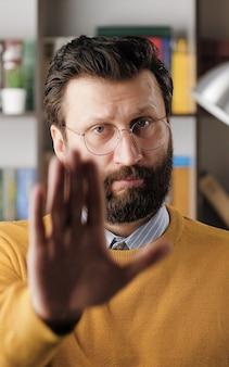 맨쇼 stop, no. 사무실이나 아파트에서 안경을 쓴 심각한 불쾌한 수염 난 남자가 카메라를 보고 손바닥을 보여줍니다. 클로즈업 보기
