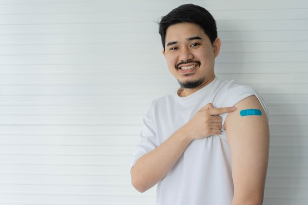 Man show strength with bandage on shoulder to expression after got coronavirus antibody vaccinated