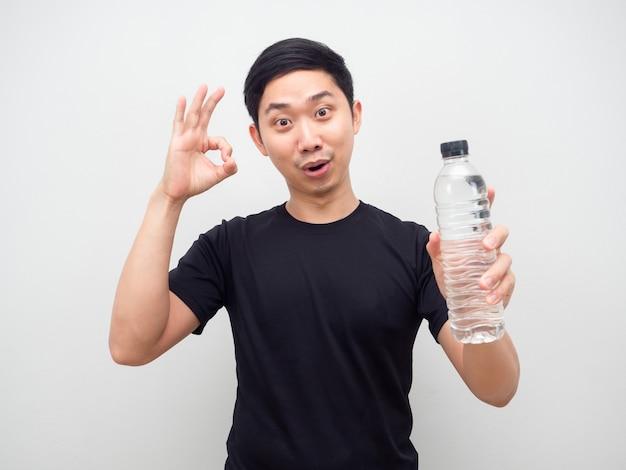 남자는 손에 물병을 보여주고 손으로 흰색 배경을 확인합니다.