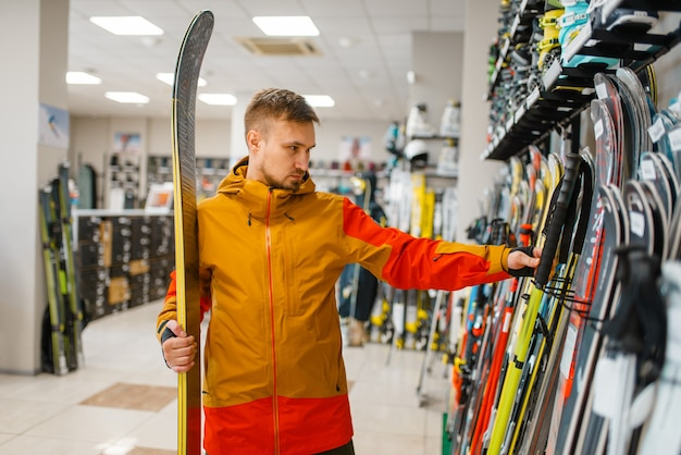 Man at the showcase choosing downhill ski, shopping in sports shop.