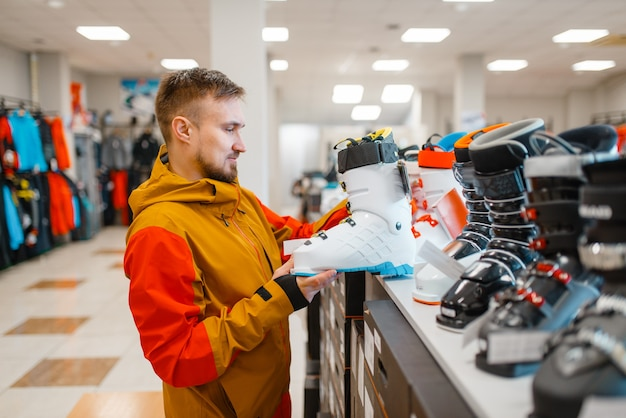 Man at the showcase choosing ski or snowboarding boots, shopping in sports shop.