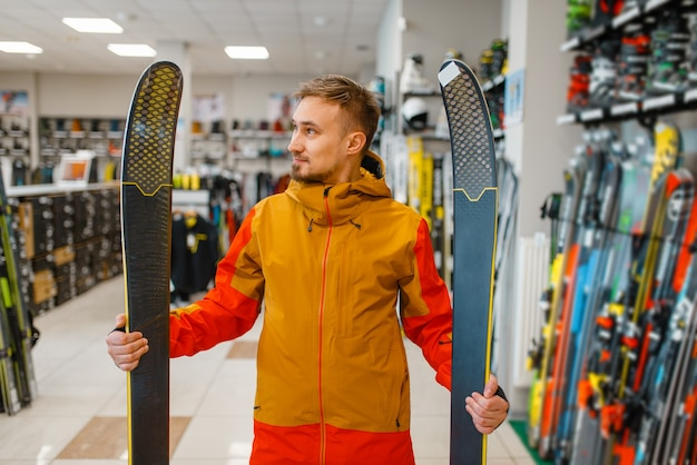 Man at the showcase holding downhill ski in hands