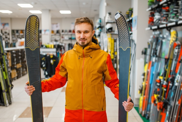 Man at the showcase holding downhill ski in his hands