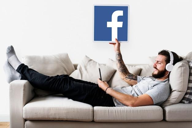 Человек, показывающий значок facebook