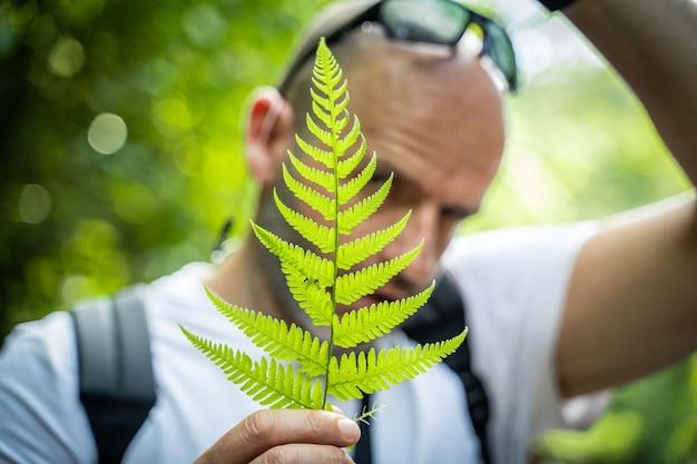 ジャングルの葉を見せている男。コスタリカ