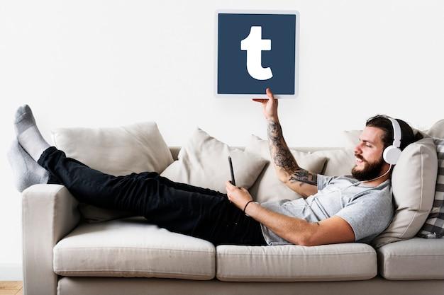 Человек, показывающий значок tumblr