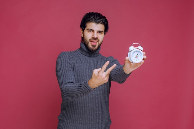 白い目覚まし時計と最高のオファーへのパッキングポイントを示している男。