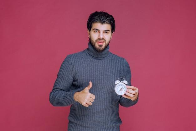 Человек показывает белый будильник и paking point к лучшему предложению.