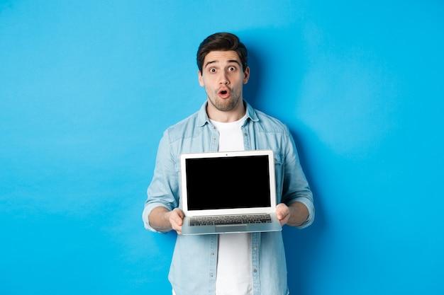 Uomo che mostra pubblicità sullo schermo del laptop e sembra stupito, dicendo wow e guardando la telecamera, in piedi su sfondo blu
