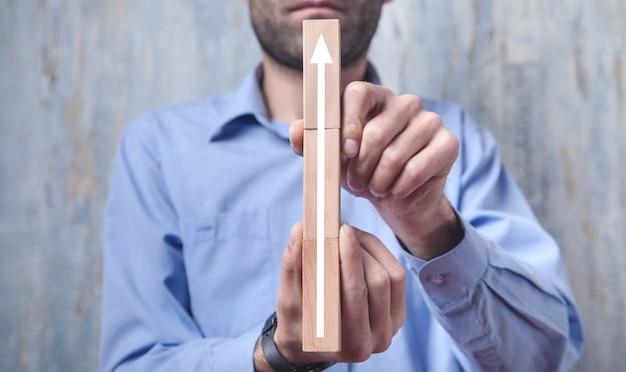 木製のブロックに矢印を示す男。ビジネス、成長、成功
