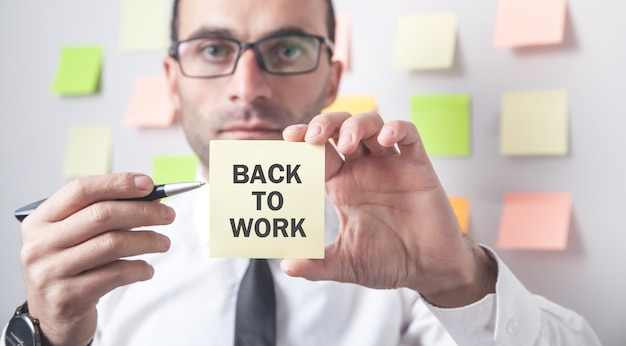 Man showing back to work text on sticky note.