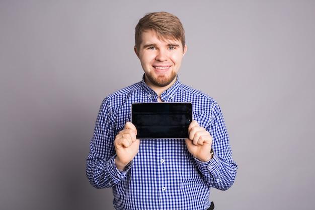 Человек показывает пустой экран таблетку на серой стене.