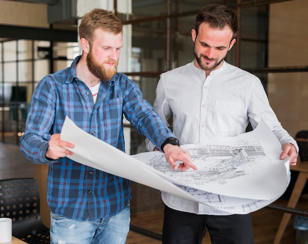 Man showing blue print to his colleague at office