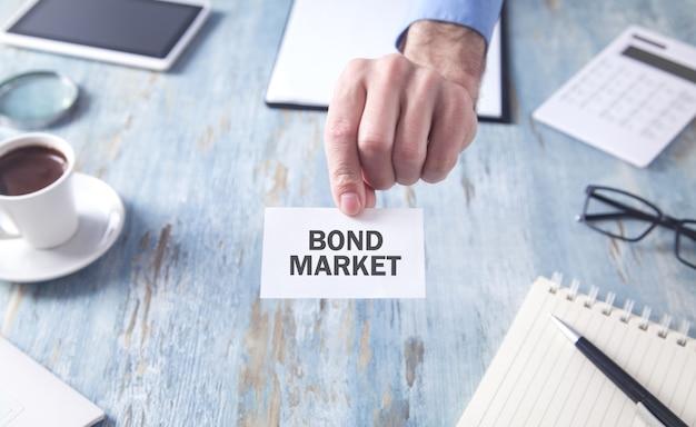 名刺に債券市場のテキストを表示している男。