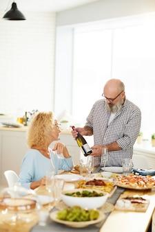 Мужчина показывает бутылку вина девушке