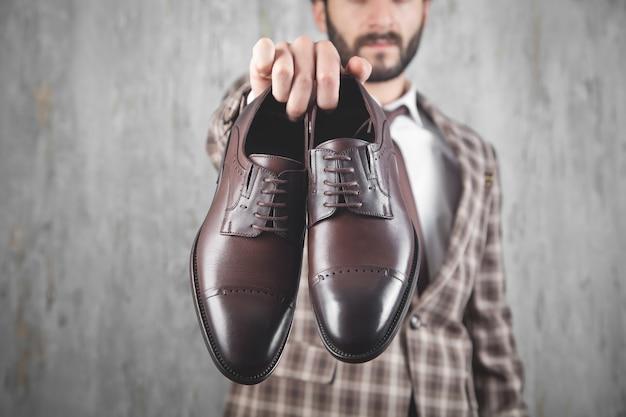 茶色の靴を見せている男
