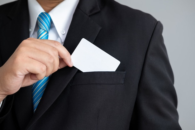 The man showing a business cards in suit
