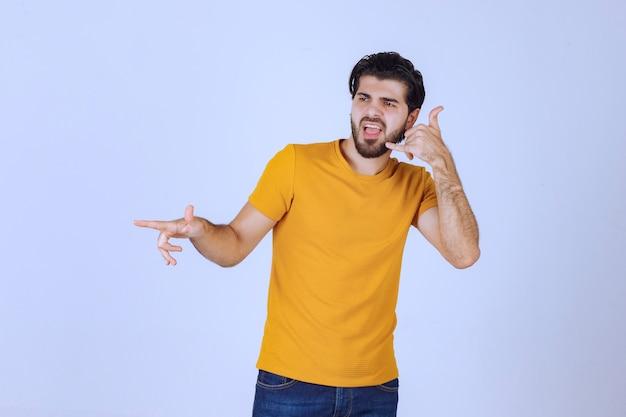 Uomo che mostra il segnale di chiamata e invita qualcuno