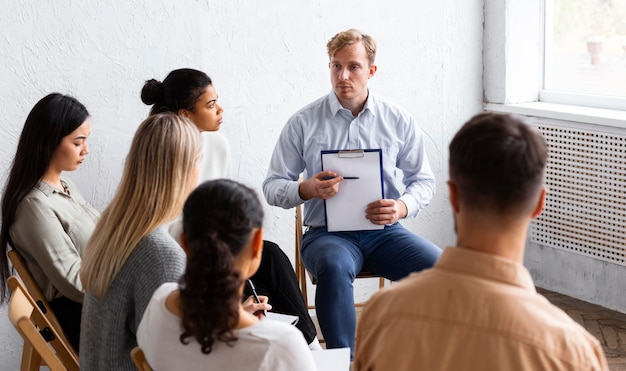 Man showing clipboard at a group therapy session