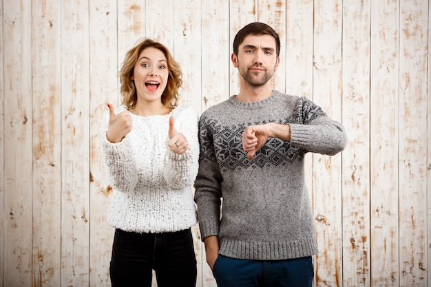 Man showing dislike girl with thumb up over wooden wall