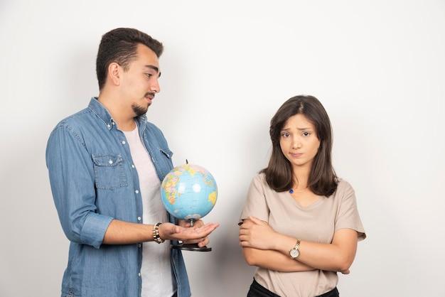 憤慨している女の子の隣に地球儀を見せている男。