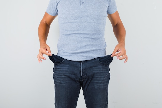 Man showing empty pockets in grey t-shirt, jeans
