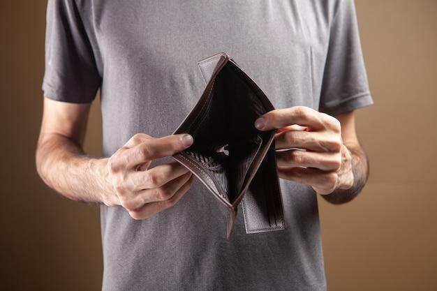 Человек показывает пустой бумажник на коричневом фоне