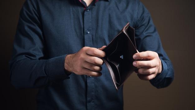 Человек показывает пустой бумажник на коричневой поверхности