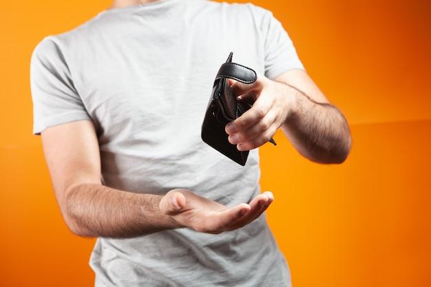 Человек показывает пустой бумажник на оранжевом фоне