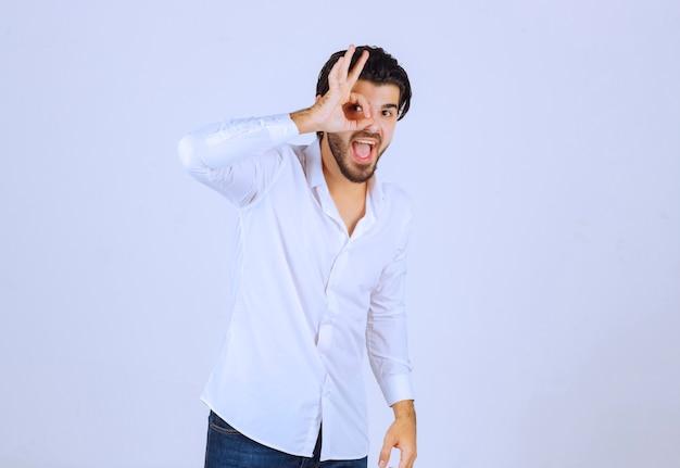Uomo che mostra il segno di godimento in una forma circolare.