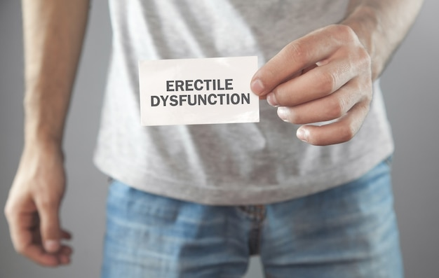Man showing erectile dysfunction text on white paper.