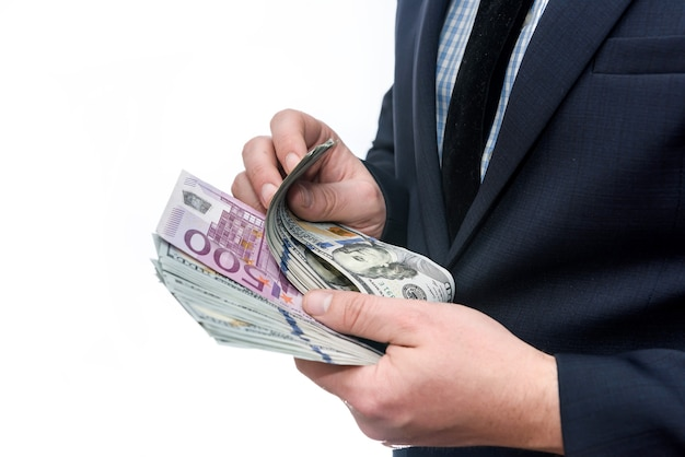 Man showing euro banknote between dollar pile