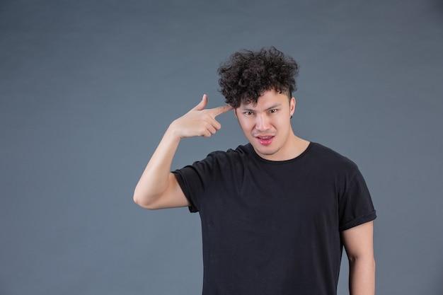 Man showing hand gesture in studio behind posing