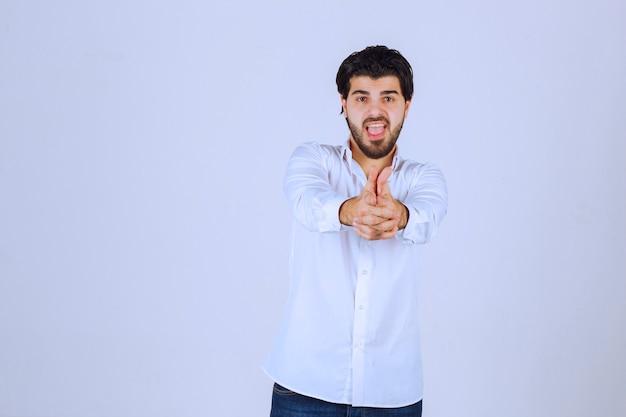 손 총 기호를 보여주는 남자.