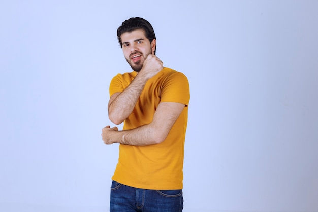 Мужчина показывает мышцы рук и чувствует себя сильным.