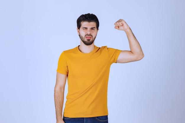 팔 근육을 보여주는 남자는 강력하다고 느낍니다.