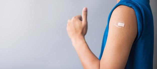 Человек показывает руку с повязкой после вакцинации
