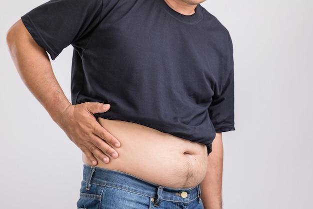 Мужчина показывает свой большой живот и боль