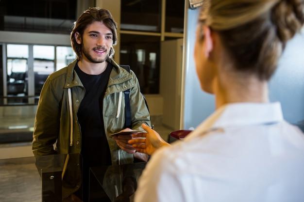 Мужчина показывает свой посадочный талон на стойке регистрации