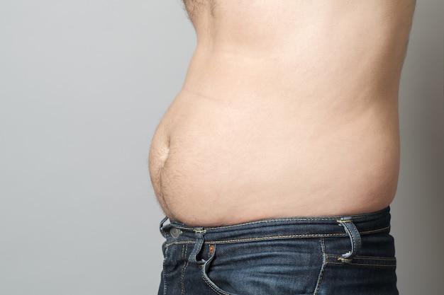 Человек показывает свой жир на животе
