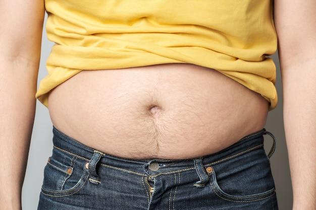 胃に脂肪を示す男性