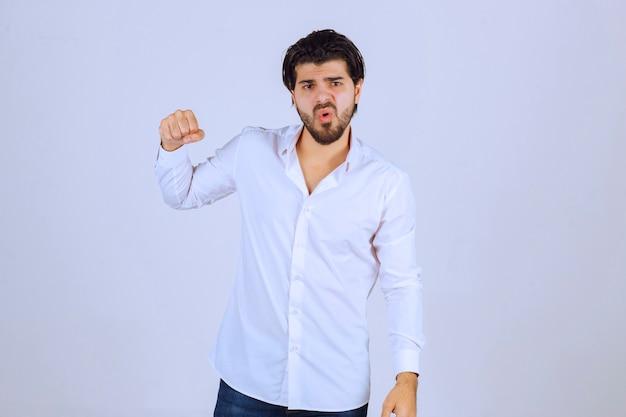 그의 주먹과 팔 근육을 보여주는 남자.