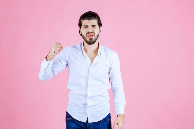 Uomo che mostra il pugno come simbolo di potere e aggressività.