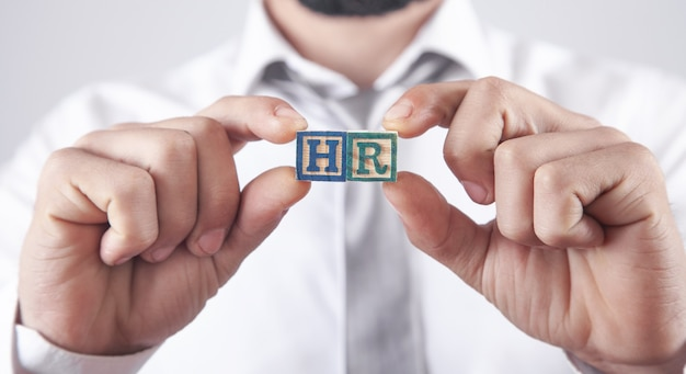 Man showing hr word on wooden cubes.